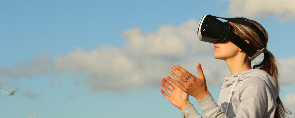Woban with VR glasses standing in front of cloudy blue sky.